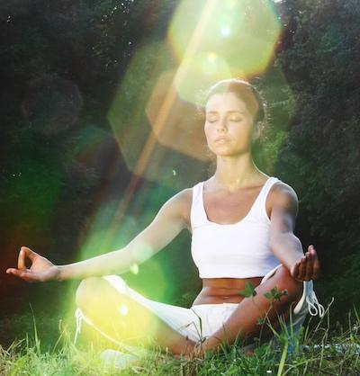 Woman meditating on grass.