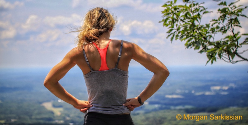 Woman trail runner at top of mountain after deep meditation running.