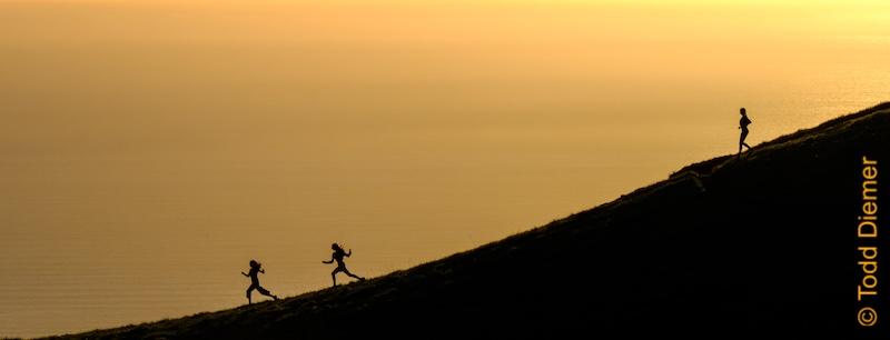 Girls enjoying running meditation down a large hill at sunset.