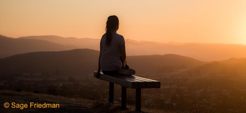 Woman meditating at sunset at night looking at mountains.